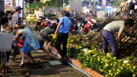 Vượt rào 'mót' hoa ở Nguyễn Huệ bất kể can ngăn của dịch vụ bảo vệ